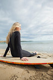Smiling beautiful blond in wet suit with surfboard at beach