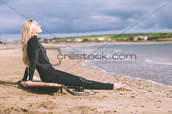 Beautiful blond in wet suit with surfboard at beach