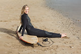 Portrait of a blond in wet suit with surfboard at beach