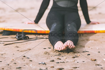 Low section of woman in wet suit with surfboard at beach