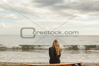 Rear view of blond in wet suit with surfboard at beach