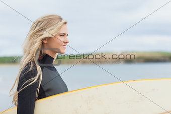 Side view of woman in wet suit holding surfboard at beach