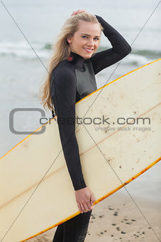 Beautiful young woman in wet suit holding surfboard at beach