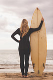 Rear view of a blond in wet suit with surfboard at beach