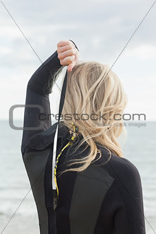 Rear view of a blond in wet suit standing at beach