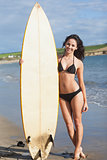 Full length of bikini woman holding surfboard at beach