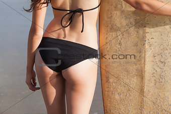 Mid section of woman in bikini bottom with surfboard on beach