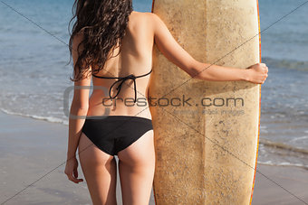 Mid section of a woman in bikini bottom with surfboard on beach