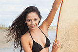 Smiling bikini woman holding surfboard at beach