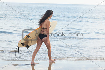 Bikini woman with surfboard walking in water at beach