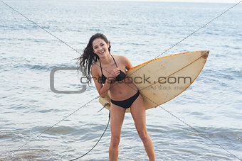 Cheerful bikini woman holding surfboard at beach