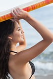 Bikini woman holding surfboard over head at beach