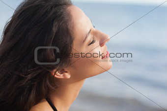 Cute young woman with eyes closed at beach