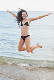 Cheerful young woman in bikini jumping at beach