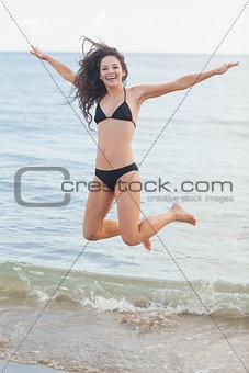 Cheerful young woman in bikini jumping at beach