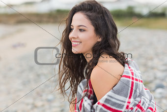 Smiling woman covered with blanket at beach