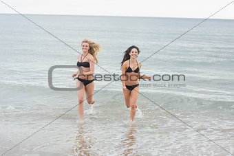 Smiling bikini women running in water at beach