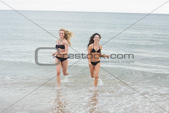 Smiling bikini women running in water at beach