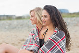 Young women covered with blanket at beach