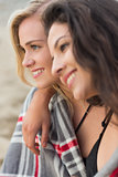 Two young women covered with blanket at beach