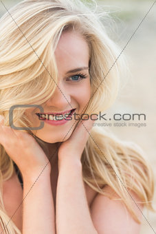 Smiling relaxed blond looking away at beach