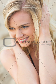 Smiling relaxed young blond looking away at beach