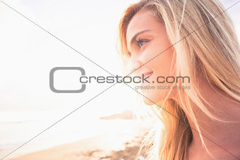 Close up of a smiling blond looking away at beach