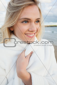 Cute smiling woman in stylish white jacket on beach
