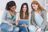 Female friends using digital tablet together on sofa