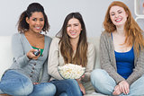 Female friends with remote control and popcorn bowl on sofa
