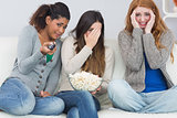 Scared friends with remote control and popcorn bowl on sofa