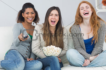 Cheerful friends with remote control and popcorn bowl on sofa