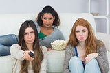 Serious friends with remote control and popcorn bowl on sofa
