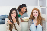 Scared friends with remote control and popcorn bowl at home