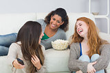 Cheerful friends with remote control and popcorn bowl at home