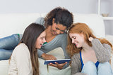 Female friends using digital tablet together at home