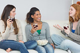 Cheerful friends with wine glasses and popcorn enjoying a conversation at home