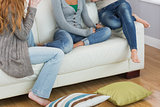 Friends sitting on sofa with cushion on floor at home