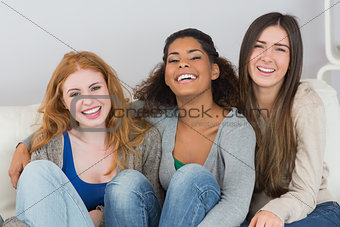 Portrait of cheerful female friends sitting at home