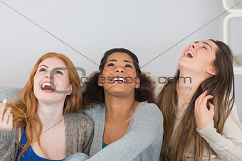 Cheerful young female friends laughing at home