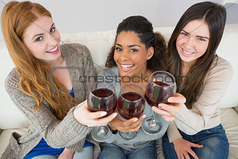 Cheerful young female friends toasting wine glasses
