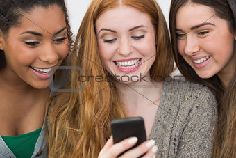 Close up of cheerful friends looking at mobile phone together