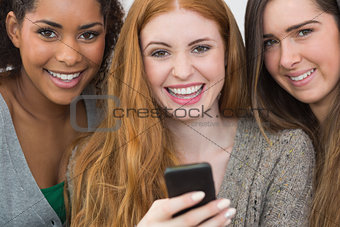 Close up portrait of cheerful friends with mobile phone