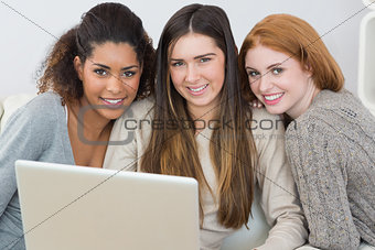Portrait of happy friends using laptop together on sofa