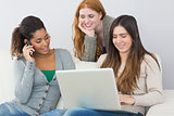 Happy young female friends using laptop and cellphone