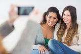 Woman photographing friends with smartphone