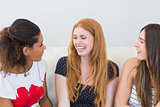 Cheerful female friends sitting on sofa at home
