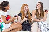 Cheerful female friends with wine glasses enjoying a conversation