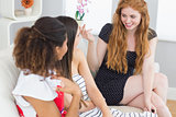 Cheerful young female friends chatting on sofa