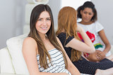 Portrait of a brunette with female friends chatting on sofa